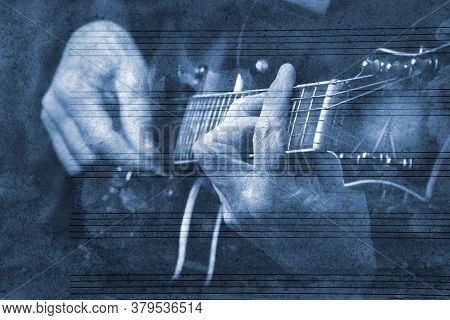 Blues Music Concept. Guitarist Playing Blues. Guitarist On The Background Of The Sheet Music.