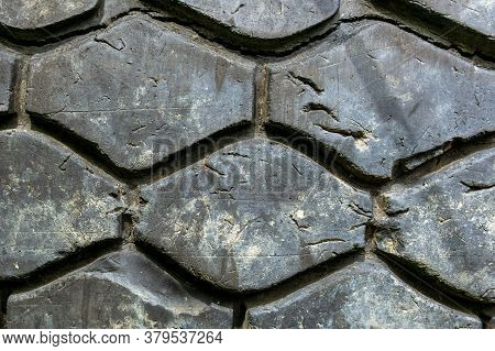 Car Tire In The Tire Repair Shop. Old Tyre In Auto Repair Service. Background Texture