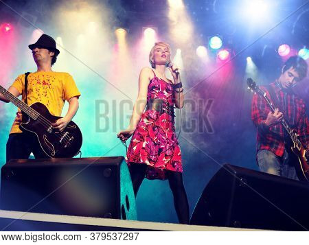 Young female rockstar Singing in Concert