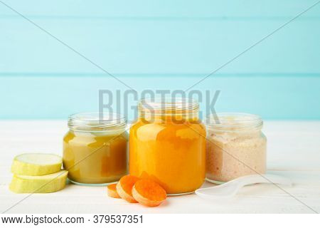 Glass Jars With Nutrient Baby Food On Blue Background. Vegetable Puree With Spoon.