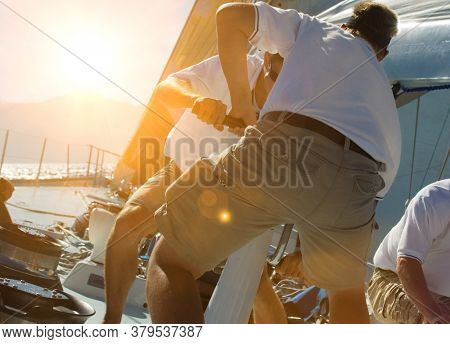 Two sailing crew members working rigging on sail boat with lens fare