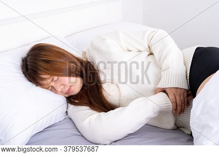 Young Woman Suffering Stomach Aches Lying On The Bed. Healthcare Medical Or Daily Life Concept.