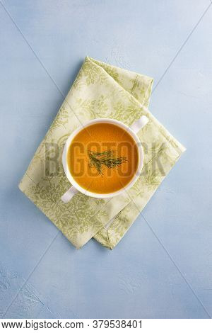 Chicken Bouillon With Thin Layer Of Fat And Dill In Soup Bowl On Green Linen Textile And On Blue Sur