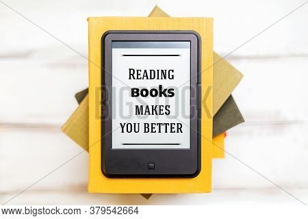 Reading And Knowledge. E-book Reader Is On Top Of A Stack Of Books On A Wooden Background. Flat Lay.