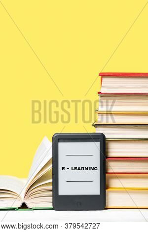 E-learning. E-book Reader And A Stack Of Books On A Yellow Background. Vertical. Copy Space. Concept
