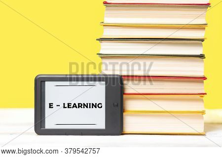 E-learning. E-book Reader And A Stack Of Books On A Yellow Background. Copy Space. Concept Of Educat