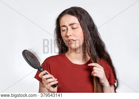 A Discontented Brunette Woman Holds A Comb With A Bunch Of Torn Hair And Looks At Her. White Backgro