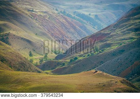 Fantasy Vast Landscape With Vivid Multicolor Clay Mountains. Off-road Car On Hill Above Scenic Mount