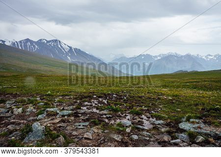 Beautiful View From Pass To Great Snowy Mountains Under Cloudy Gray Sky. Dramatic Alpine Landscape W