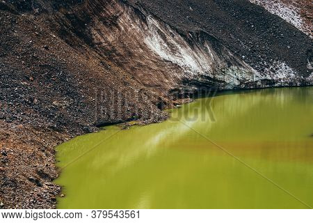 Stones On Slope Of Glacier Above Mountain Lake Of Acid Green Color. Beautiful Emerald Glacial Lake A