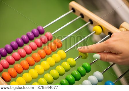 Closeup Female Hand Calculating With Balls On Wooden Rainbow Abacus For Number Calculation. The Conc