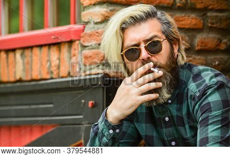 Hipster Smoking Old Architecture Background. Medical Cannabis. Brutal Guy Sunglasses Smoking Tobacco