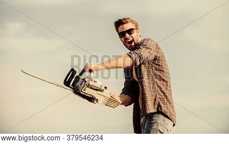 Sharp Blade. Dangerous Job. Feeling Manly. Powerful Chainsaw. Handsome Man With Chainsaw Blue Sky Ba