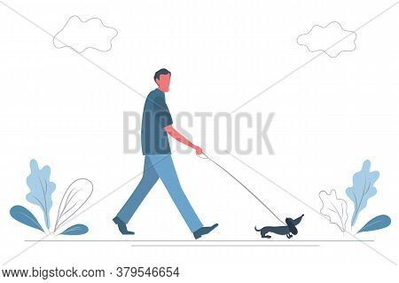 Man Walks With A Dog In The Park.a Man Leads A Dachshund Dog On A Leash. There Are Also Plants And C