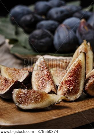 Pieces Of Figs On A Wooden Board, At The Bottom Figs On A Tray With The Leaf Of The Fig Tree