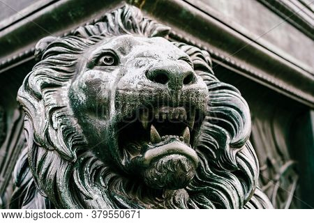 A Lion Figure Carved From Stone On A Building.