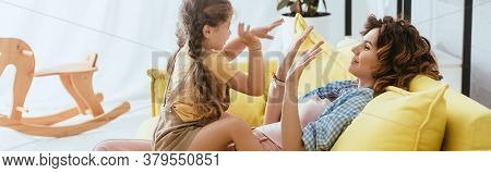 Shot Of Child And Babysitter Playing Pat-a-cake Game While Sitting On Sofa