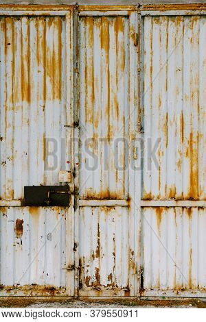 Old Metal Gate With Peeling Paint And Rust And An Iron Bolt.