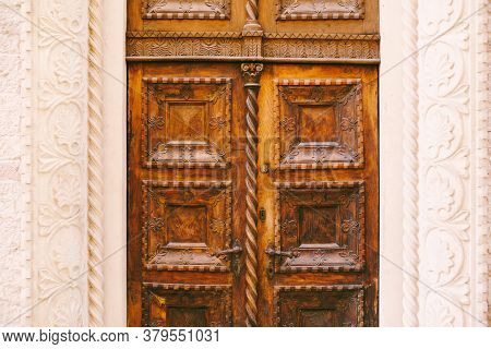 A Close-up Of Brown Doors With Raised Carvings And Patterns In A White Molded Opening.