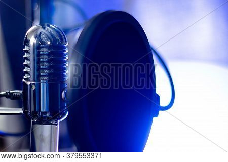Microphone With Pop Filter On Blue Background. Studio