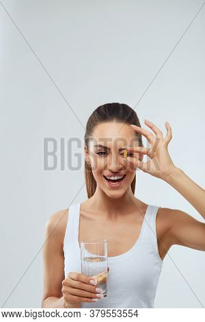 Portrait Of Beautiful Woman Taking Vitamin Pill With Glass Of Fresh Water Indoors. Smiling Girl Taki