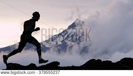 Running man athlete trail running in mountain summit background. Male runner on run training outdoors living active fit lifestyle. Silhouette at sunset.