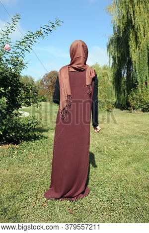 Woman In A Hijab. Girl In Traditional Muslim Brown Clothes On A Background Of Green Grass. Stands Wi