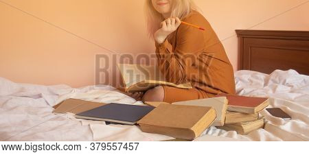White Cozy Bed And Girl Reading Books. Woman Sitting On The Bed And Reading