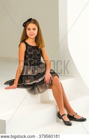 Beautiful Little Girl Is Sitting In The Studio On A White Staircase. Style And Fashion Concept, Happ