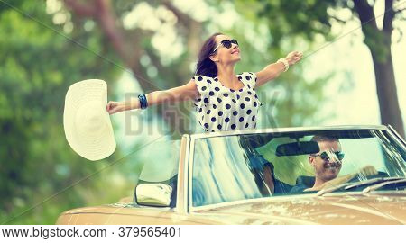 Happy Couple On A Summer Roadtrip With Girl Sitting On Top Of A Convertible Back Seat, Arms Open, Ha