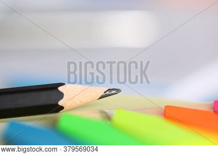 Close-up Of Black Pencil Laying On Desktop. Office Accessories And Colourful Bookmarks. Detailed Pic