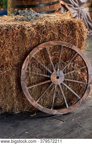 An Old Wooden Wheel From A Cart Near A Haystack. The Village, The Village Decor.
