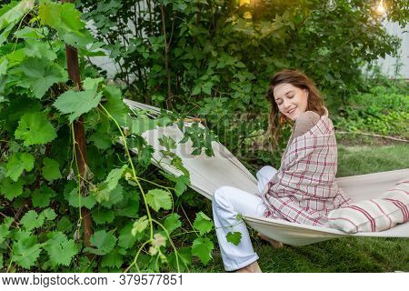 Brunette In White Pants Wrapped In A Blanket In A Hammock On A Street On A Background Of Green Plant