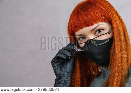 A Red-haired Girl In A Black Cloth Mask, Black Medical Gloves And Glasses Looks Into The Frame. A Yo