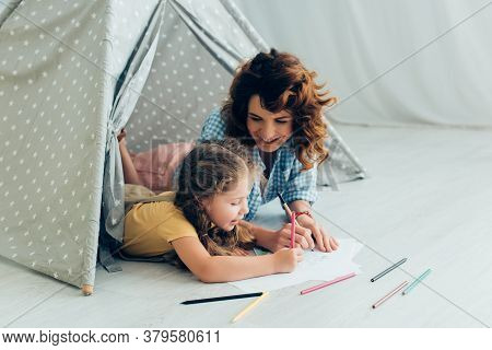 Babysitter And Adorable Child Drawing Together While Lying In Play Tent