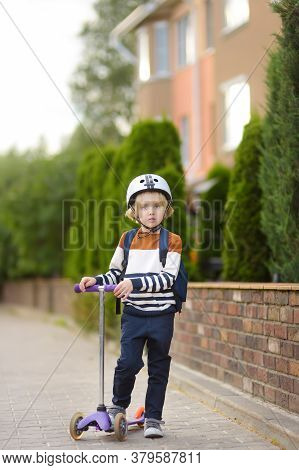 Little Boy In Safety Helmet Riding Scooter To School. Quality Protect Equipments For Safety Kids On