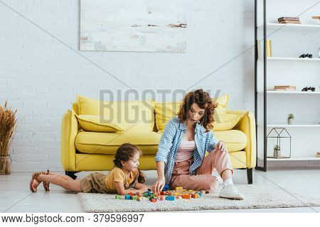 Nanny And Cute Child Playing With Multicolored Blocks On Floor Near Yellow Sofa