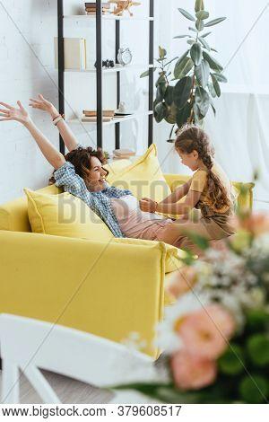 Focus Of Kid Tickling Laughing Babysitter While Having Fun On Sofa
