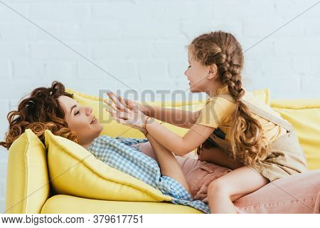 Child Playing Pat-a-cake Game With Lying Nanny While Having Fun On Sofa