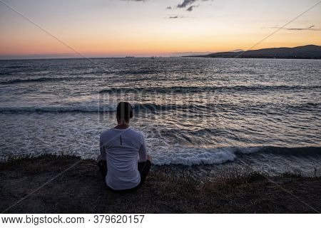 At Sunset, The Guy Sits On The Edge Of A Cliff And Looks At The Beautiful Seascape And Waves. Rest A