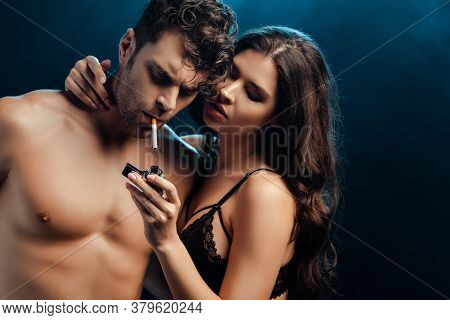 Sexy Woman In Bra Holding Lighter And Embracing Boyfriend With Cigarette On Black