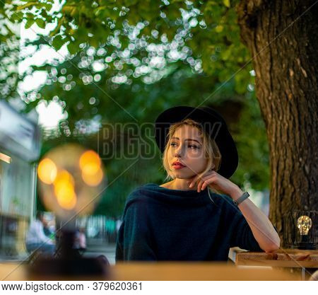 Beautiful Blonde Woman Portrait Tender Looking Side Ways Fashion Style Of Cloth In Patio Cafe Table