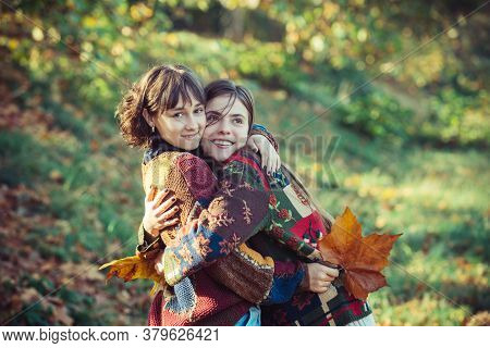 Girl Hugging Her Best Friend. Two Beautiful Girls Friends In Autumn Park. Beautiful Young Girls With