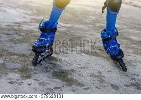 Little Boy Learning Roller Skate By Wearing Blue Roller Skate Shoes And Knee Pads For Safe.