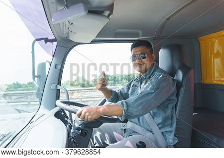 Professional Truck Driver, Adult Male Asian Wearing Sunglasses Smile And Raise Your Hand. The Young