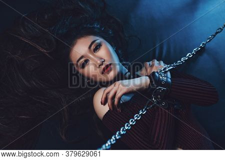 Young asian woman with chain sexy bdsm style portrait. Male hand holding chain.