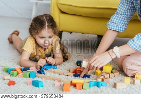 Partial View Of Babysitter And Kid Playing With Multicolored Blocks Of