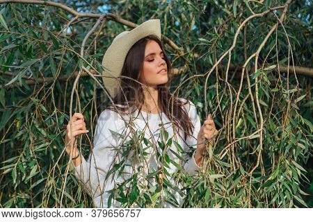Young Beautiful Brunette Woman Standing Close To The Tree Brunches With Green Leaves