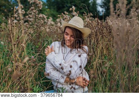 Young Beautiful Brunette Woman Sitting On The Grass, Smiling And Touching Her Hair