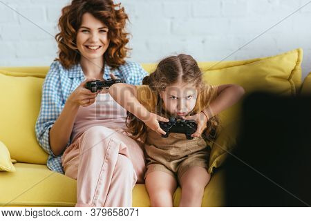 Kyiv, Ukraine - June 19, 2020: Selective Focus Of Smiling Babysitter And Concentrated Child Playing